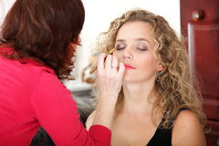 Make up artist applying makeup to a fashion model Stock Photo
