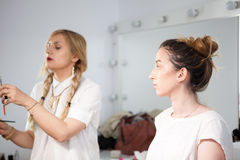 Make-up artist applying makeup to a model Royalty Free Stock Photography