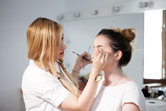 Make-up artist applying makeup to a model Stock Images