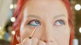 Make-up artist applying makeup to model`s eye. Close up view. stock photo