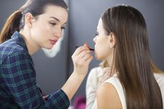 A make-up artist is applying makeup to a young girl. stock photos