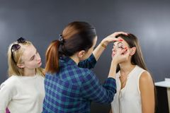 The make-up artist is applying makeup to the young girl. royalty free stock photography