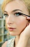 Make-up artist applying mascara  on model's eye Stock Photos