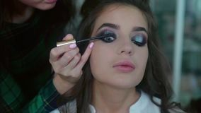 Make up artist applying on mascara on model`s eyes stock video footage
