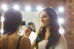 Make-up artist applying powder with a brush on model's cheeks, r Royalty Free Stock Photography