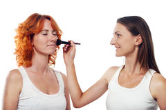 Make-up artist applying powder on model's face Royalty Free Stock Photography