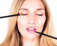 Make-up artist applying shadows and shine with cosmetic brushes. Close up. Royalty Free Stock Photography