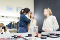 A make-up artist is applying makeup to a young girl. royalty free stock photography