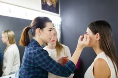 A make-up artist is applying makeup to a young girl. stock photography
