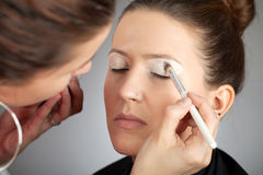 Make-up artist applying white eye shade Royalty Free Stock Images