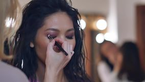 Make-up artist with an Asian appearance. Close up view. Smoky eyes. Slow motion stock video