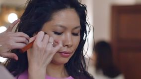 Make-up artist with an Asian appearance. Close up view. Smoky eyes. Slow motion stock footage