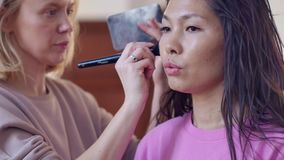 Make-up artist with an Asian appearance. Close up view. Smoky eyes. Slow motion stock video footage