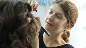 Make-up artist is causing a eye-shadow on the model using the brush stock footage