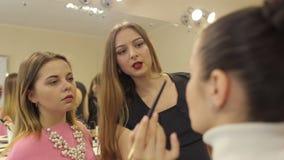 Teacher helps girl do a makeover in beauty salon.