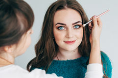 Make-up artist does the make-up of the girl. Make-up artist puts shadows on eyes stock photo
