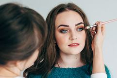 Make-up artist does the make-up of the girl. Make-up artist puts shadows on eyes royalty free stock image