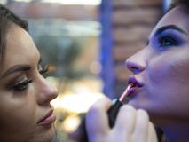 The make up artist does make up to the beautiful young woman indoors.lips close up royalty free stock images