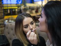 The make up artist does make up to the beautiful young woman indoors.professional paints lips with lipstick. The make up artist does make up to the beautiful royalty free stock photography