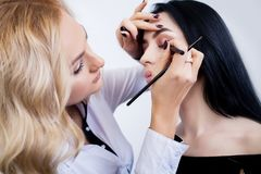 Make-up artist does makeup to a beautiful girl in a beauty salon Royalty Free Stock Image