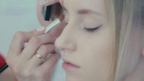 Make-up artist does pearlescent shade on the eyelid using a brush stock video footage