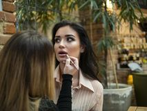 The make-up artist does make up to the beautiful young woman indoors.professional paints lips with lipstick. The make-up artist does make up to the beautiful stock photo