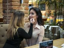 The make up artist does make up to the beautiful young woman indoors.professional paints lips with lipstick. The make up artist does make up to the beautiful royalty free stock images