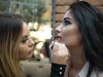 The make up artist does make up to the beautiful young woman indoors.professional paints lips with lipstick. The make up artist does make up to the beautiful royalty free stock image