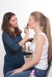 Make-up artist doing make-up of a beautiful young Stock Photos