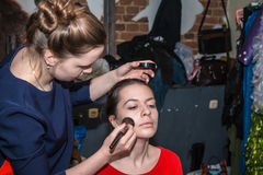 Make-up artist doing the make-up for nice girl Royalty Free Stock Images