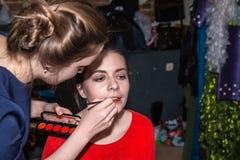 Make-up artist doing the make-up for nice girl Stock Photos
