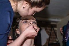 Make-up artist doing the make-up for nice girl Stock Photo