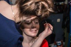 Make-up artist doing the make-up for nice girl. Make-up artist doing the make-up for beautiful girl Stock Photography
