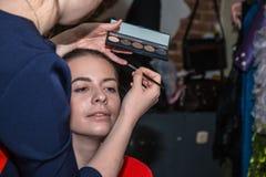 Make-up artist doing the make-up for nice girl. Make-up artist doing the make-up for beautiful girl Stock Photo