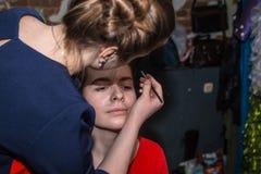 Make-up artist doing the make-up for nice girl. Make-up artist doing the make-up for beautiful girl Royalty Free Stock Image