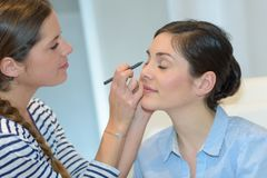 Make-up artist doing make-up to client in salon Royalty Free Stock Photo