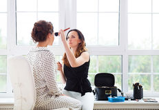 Make-up artist doing make up for young beautiful bride stock photography
