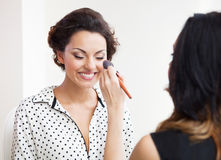 Make-up artist doing make up for young beautiful bride Royalty Free Stock Photos