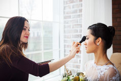 Make-up artist doing make up for young beautiful bride royalty free stock photography