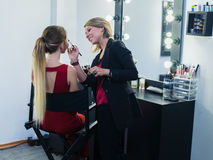 Make-up artist doing makeup to beautiful young girl Royalty Free Stock Photography