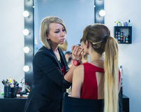 Make-up artist doing makeup to beautiful young girl Royalty Free Stock Photo