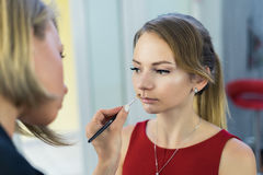 Make-up artist doing makeup to beautiful young girl. In the studio. Sad model Royalty Free Stock Image