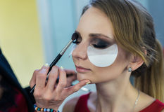 Make-up artist doing makeup to beautiful young girl royalty free stock images