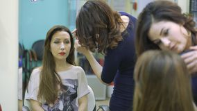 Make-up artist doing a model`s makeup at the salon stock video footage