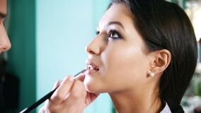 Make up artist doing professional make-up lips for attractive young model stock video