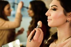 Make up artist doing professional make up of young woman. School of make-up artists stock images