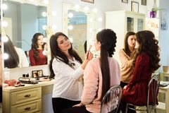 Make up artist doing professional make up of young woman. School of make-up artists royalty free stock images