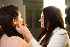 Make up artist doing professional make up of young woman. School of make-up artists stock photos