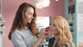 Make up artist doing professional   of young woman, brush in stylist hands. Royalty Free Stock Image