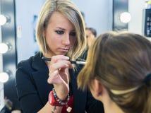 Make-up artist doing smoky eyes makeup to beautiful young girl Royalty Free Stock Image